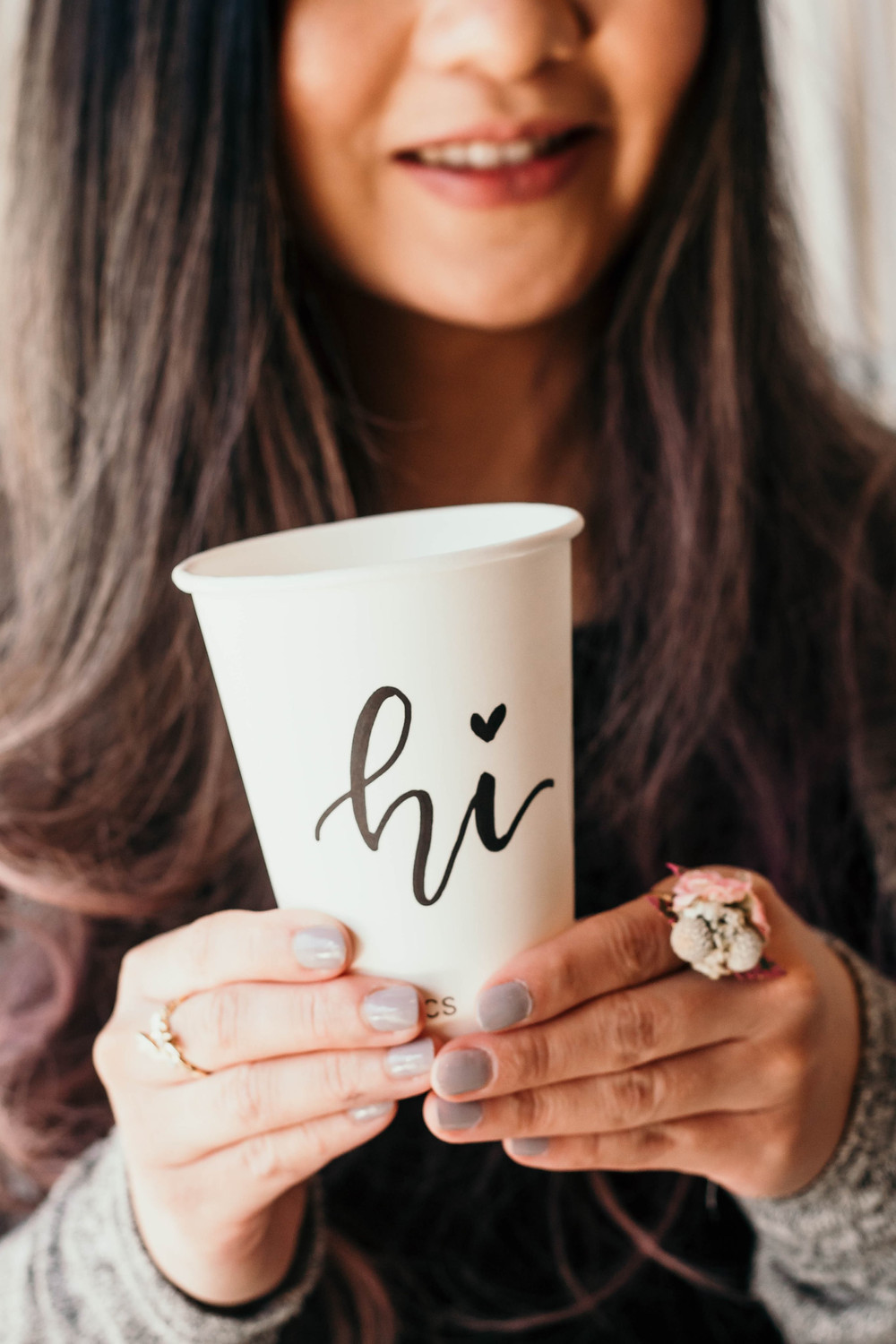 A hand lettered coffee cup is held by a hand wearing a floral ring