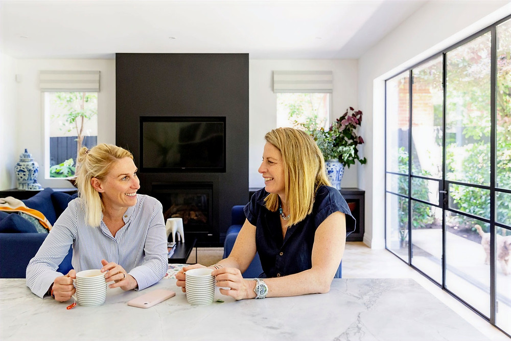 The Interior Design Process - Consultation Phase. Image is of two women sitting at a bench have a disccussion over a coffee.