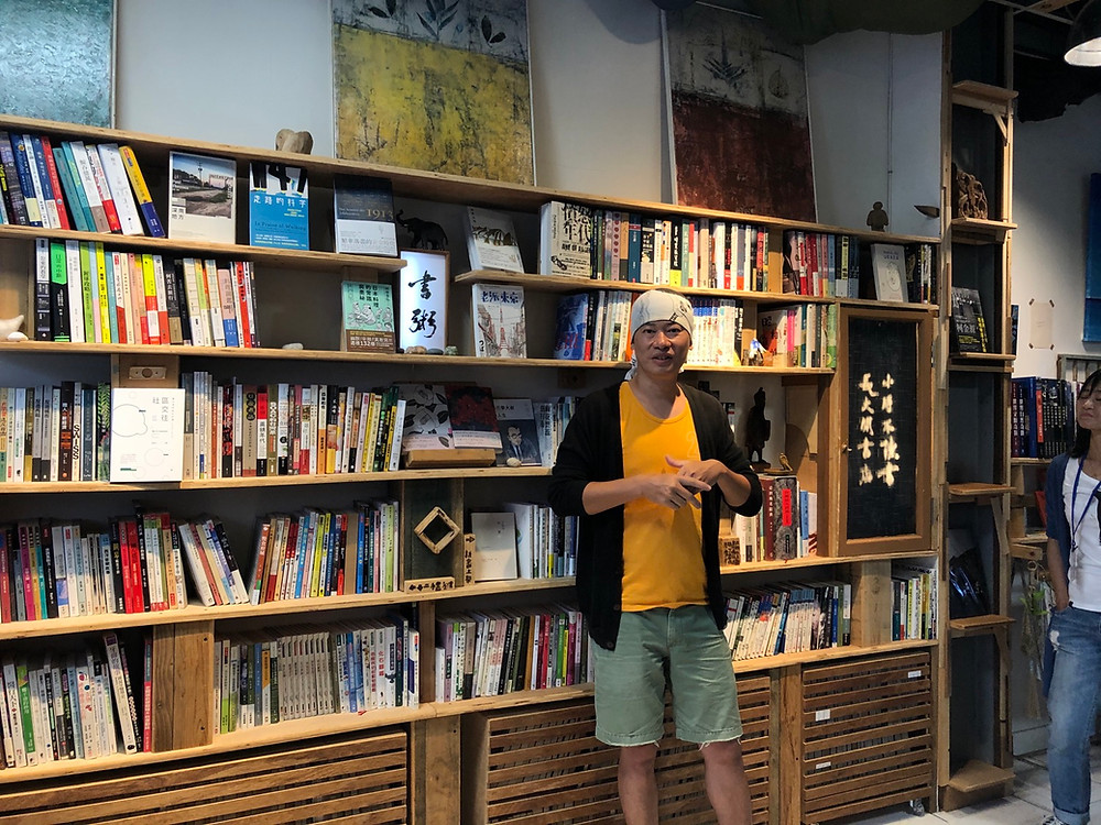 Gao Yaowei, the owner of Book Porridge Bookstore in Changbin, stands in front of his exotic collection of books.