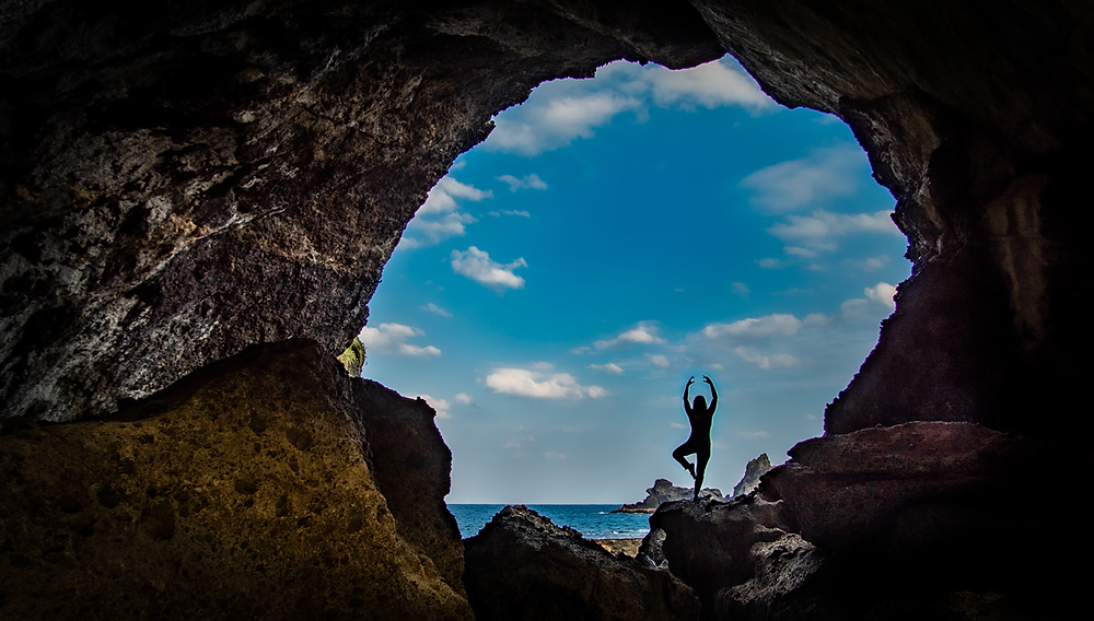 Woman's silhouette inside a round hole in the Wangong Cave, Green Island, which was created by natural sea erosion