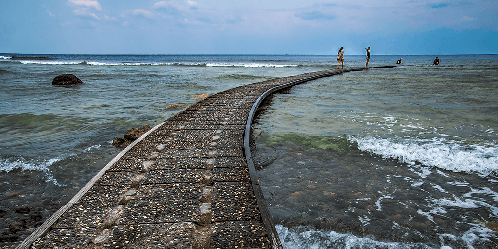 A curved, man-made walkway above the ocean that leads into the popular shore diving spot at Shilang Beach, Green Island