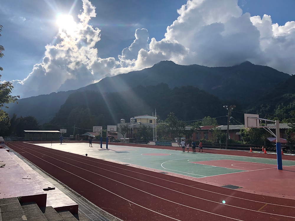 Picture of a school track in the Dabang village with the Alishan mountain range in the background.