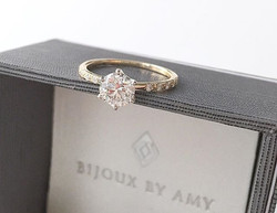 A round brilliant diamond embraced by a 6-prong setting on a delicate yellow gold band embedded with