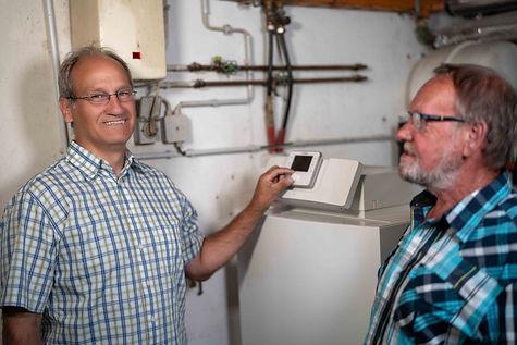 Thomas Müller erklärt dem Kunden Energieersparnis bei der richtigen Einstellung der Heizungsanlage