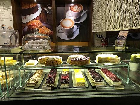 Kuchentheke mit Torte und Stückchen