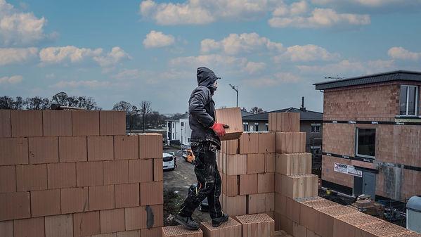 Baustelle Arbeiter trägt Baustein WEB.j