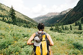 Girl with yellow backpack and hiking gear walking towards mountains
