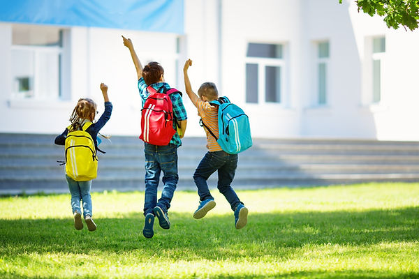 Children with rucksacks jumping in the p