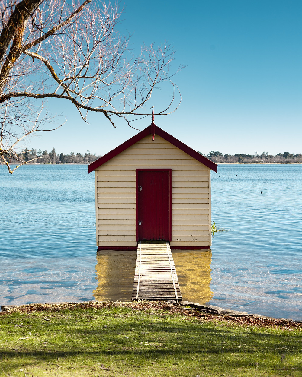 a simple wooden shed built on a water lake