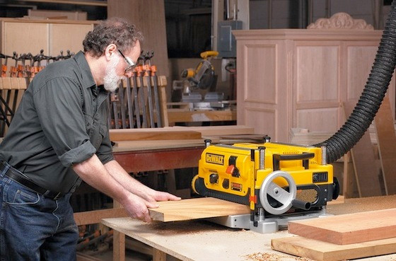 a carpenter working on a thickness planner