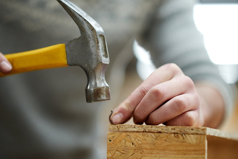 a hammer pound a piece of wood