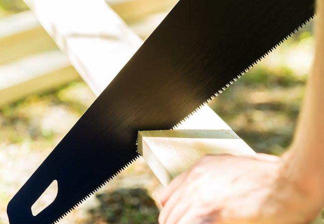a handsaw cutting wood