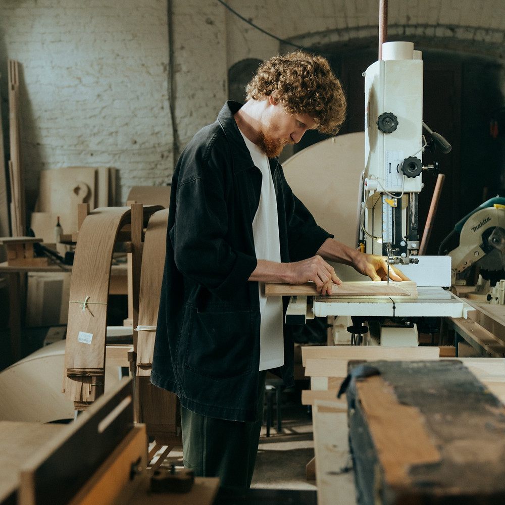 a woodworker working a saw in his workshop