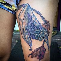 Spooky skeleton autumn bat skull thigh tattoo