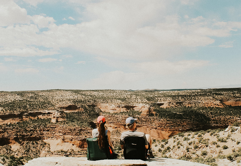 A couple sitting in camping chairs in a dessert in Colorado on a backpacking trip in September.