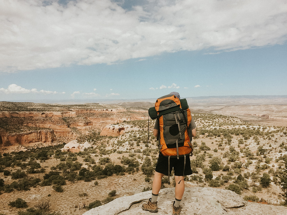 The view of a backpacker on a backpacking trip n the Black Ridge Canyons Wilderness area in Colorado on a blue sky day.