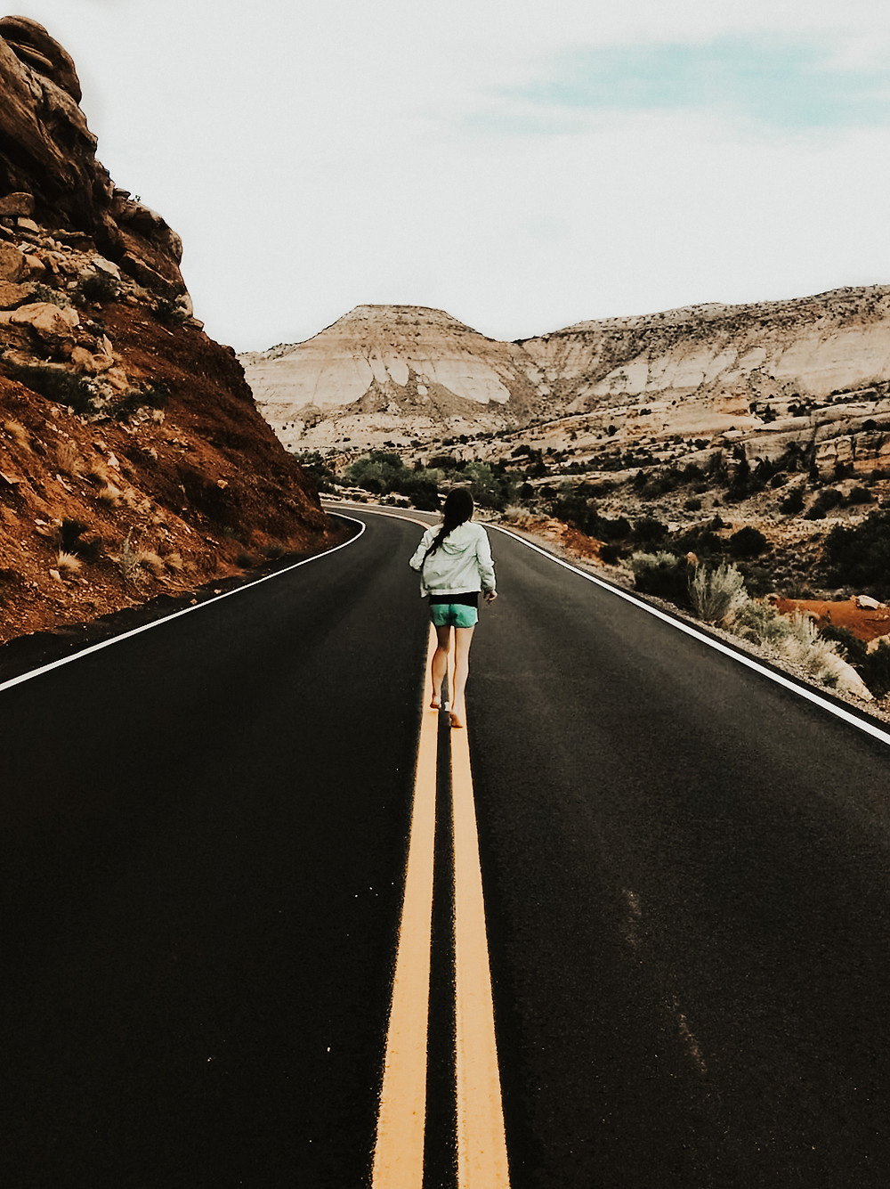 Running on the yellow lines of the winding road through the Colorado National Monument park in Colorado.