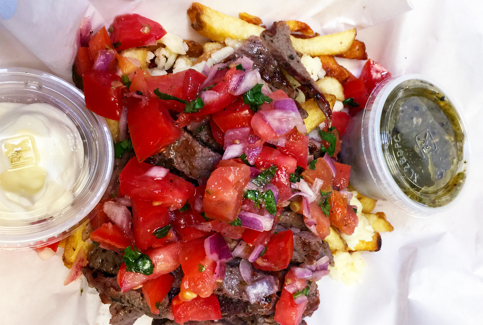 Carne Asada Fries with sour cream and green salsa