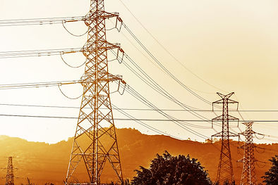 electricity-transmission-pylon-silhouetted-against-blue-sky-d-scaled.jpg
