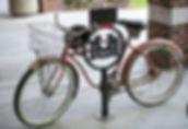 red bike locked to bike rack with UM logo