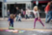 2 young girls playing in street blowing bubbles during Sunday Streets