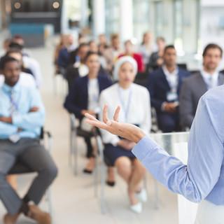 female-speaker-speaks-to-business-people