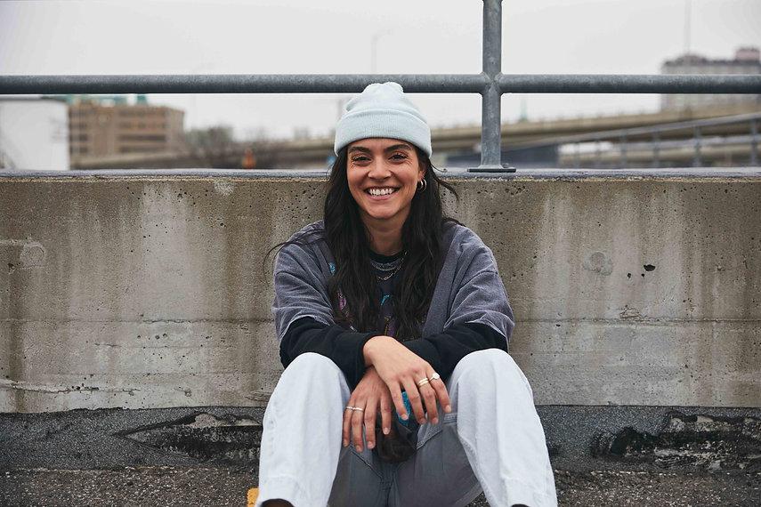 young-woman-smiling-sitting-concrete-par