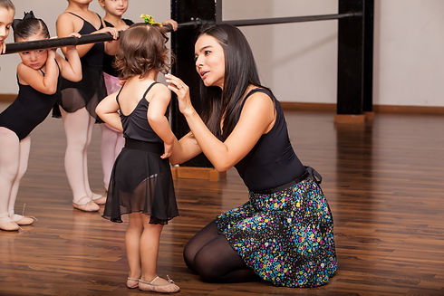 young female dance instructor comforting a young dance student