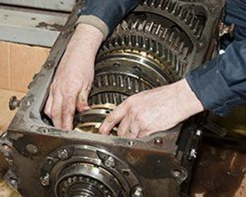 mechanic with hands on gearbox interior