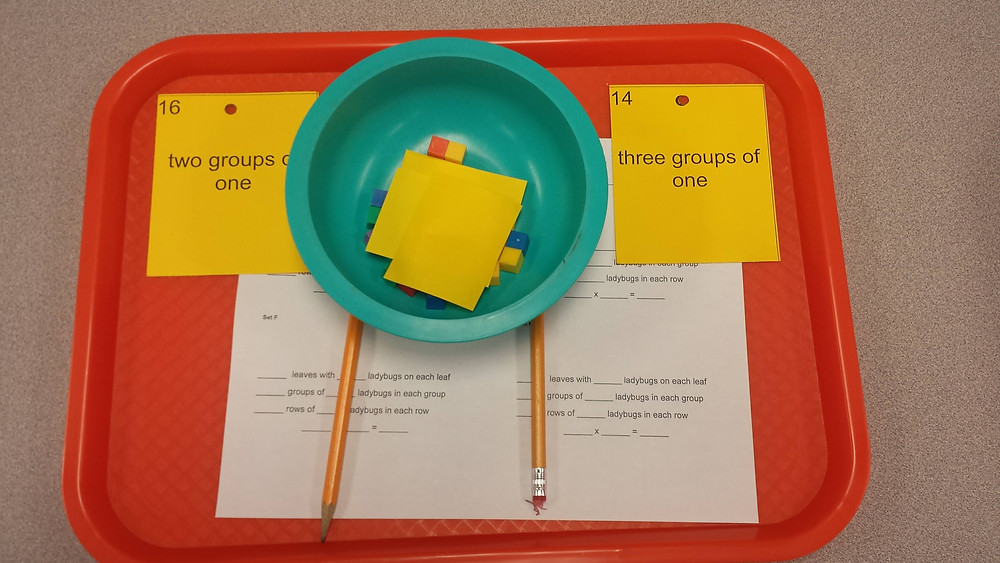 In the Math Lab we use cafeteria trays to prep for classes. All the materials students will need are on the tray, so switching between back to back classes, whether second grade or sixth is a breeze. Plastic cereal bowls hold smaller manipulatives or dice.    This tray features materials for a third grade modeling multiplication lesson. Students modeled groups using squares of paper for the group and cubes for the members in the groups. The lesson also featured a Wall Work activity where students found the image that matched their yellow card on the wall around the room.