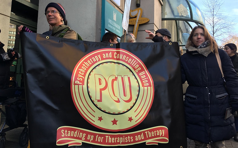 Image of two PCU members holding the PCU banner at a demonstraion