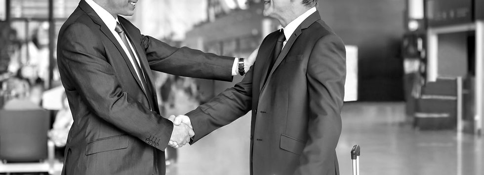 30530164_mature-businessman-shaking-hands-with-business-partner-in-airport_edited.jpg