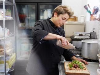 A female chef drizzling balsamic vinegar
