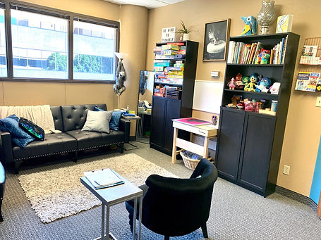 An office is shown with a couch against a large open window. There are many games, books, & toys.
