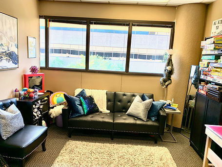 Couch with pillows, blankets, plush toys, and fidgets against a large open window inside an office.