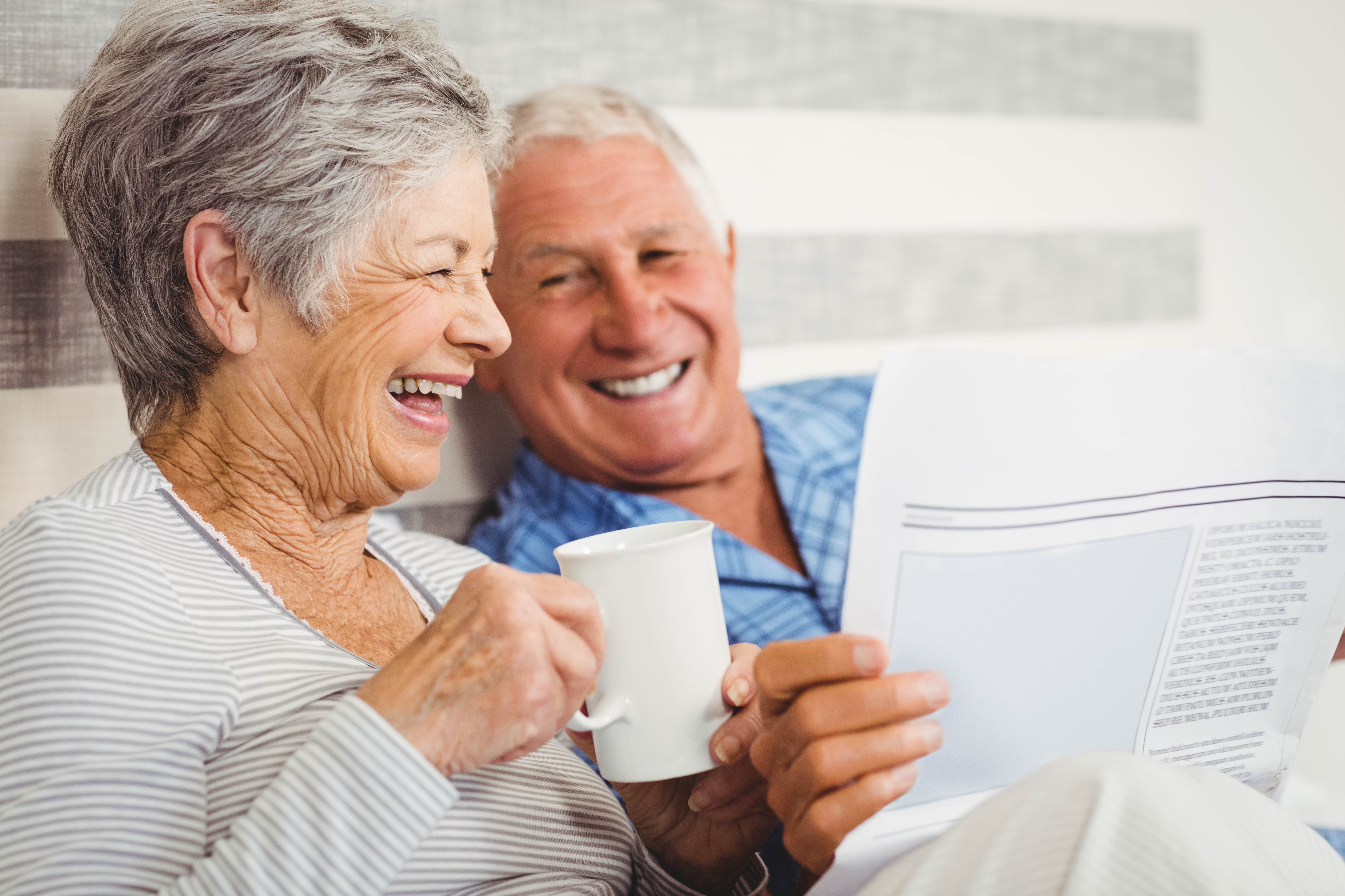 Senior couple laughing while reading new