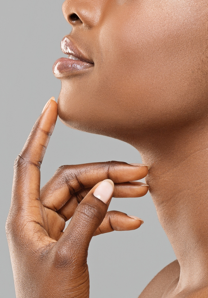 A woman with beautiful skin rests the fingers of her left hand on her chin and neck.