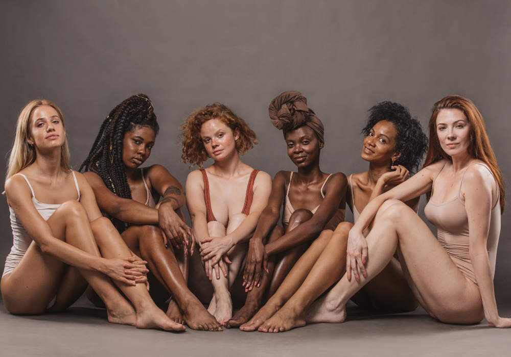 A group of women from different ethnic backgrounds sit together against a gray background. The women are wearing neutral-toned leotards and look relaxed.