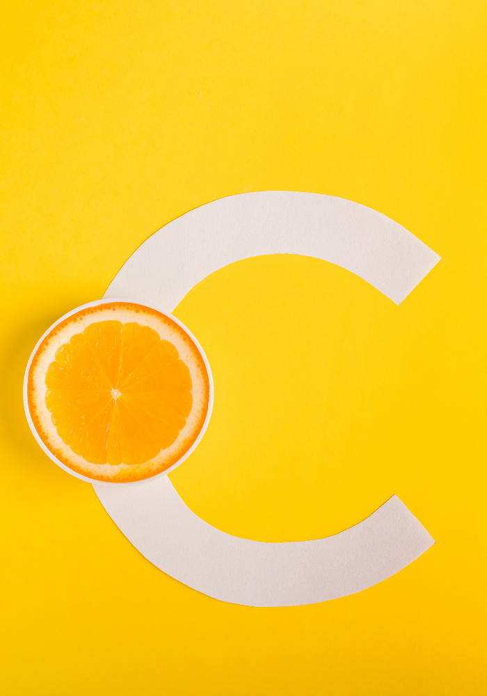 """A large white letter """"C"""" rests against a bright yellow background. In the middle of the letter is an orange sliced in half."""