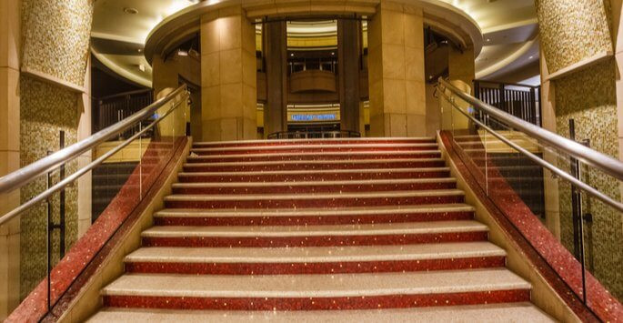 The steps of the Dolby Theater. The steps are marble with pink glitter separating each step. The stairs lead up to a golden marble foyer.