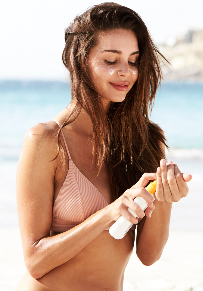 A smiling woman in a pink bathing suit smiles as she applied sunscreen at the beach.