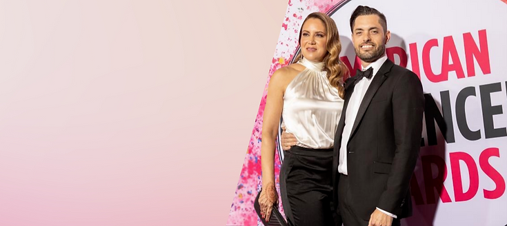 "Dr. Sarah Yovino and Dr. Justin Yovino pose in front of a sign reading ""American Influencer Awards."" Dr. Justin wears a black tuxedo, and Dr. Sarah wears a white satin top with black satin pants. She holds a black clutch in her hand, which is decorated with a henna design."