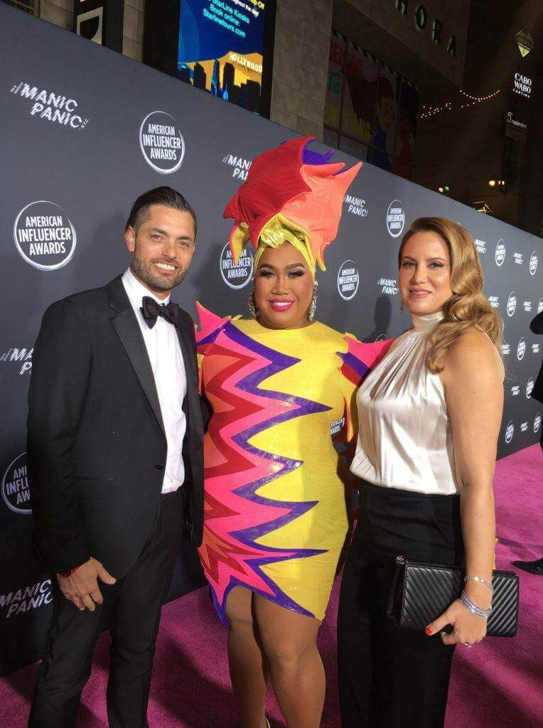Dr. Justin Yovino and Dr. Sarah Yovino decked out in formalwear pose with Patrick Starr on the pink carpet at the American Influencer Awards. Patrick wears a colorful sequined dress and a starfish-themed headdress.