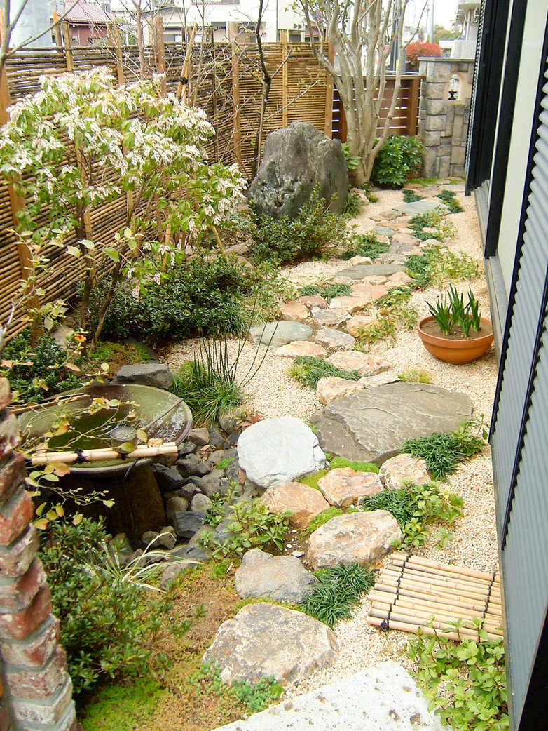 大きさの異なる飛び石を上手に組み合わせた園路に、地被植物をリズム感よくデザインした和風の庭。