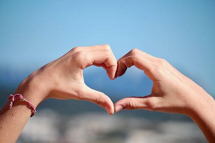 ידיים שיוצרות תמונה של לב, מסמלות תרומה מכל הלב לאבוקת אור