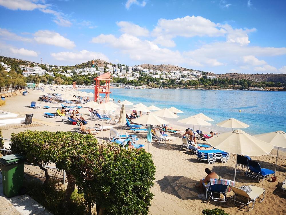 Blick aufs Meer und über das Strandbad mit Liegen und weißen Sonnenschirmen.
