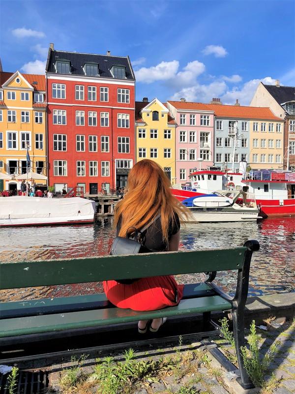 Nyhavn Kopenhagen Mädchen sitzt auf Bank