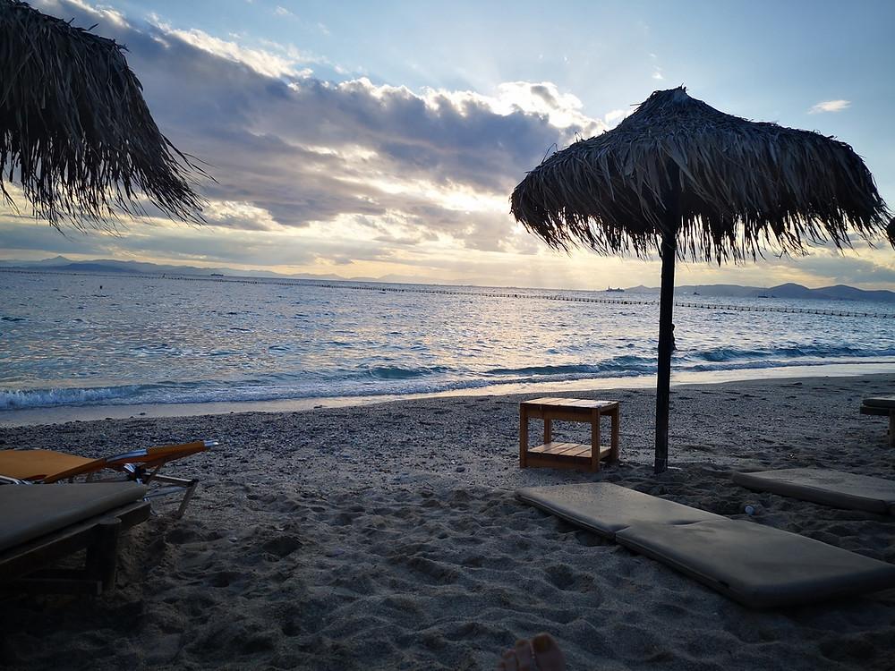 Sonnenuntergang in der Bolivar Beach Bar. Keine Gäste, leerer Strand, die Schirme aus Palmenblättern wiegen sich im Wind
