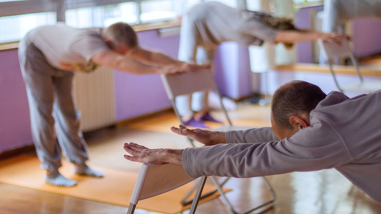 Yoga class, downward facing dog with the help of a chair done by three practitioners._edited.jpg