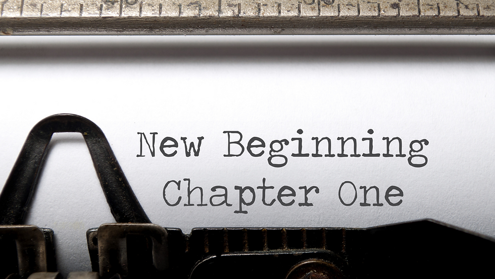 "paper in typewriter, with the typed words ""New Beginning Chapter One"""